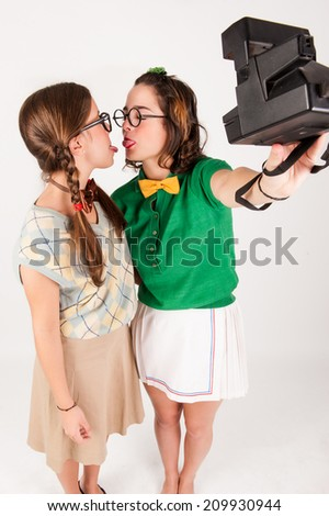 Young nerdy girls taking a selfie with instant camera. studio shot. - stock photo