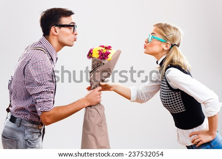 Young nerdy man is giving a bouquet of flowers to his nerdy lady,Flowers for my nerdy lady! - stock photo