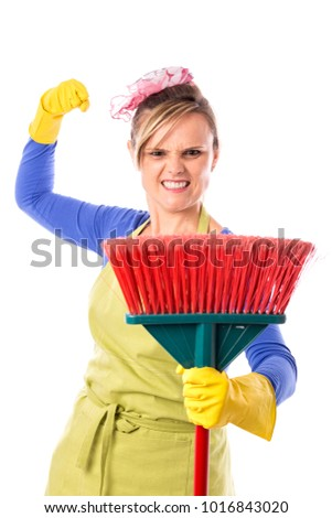 Young nervous housewife with yellow rubber gloves and apron holding a broom over white background