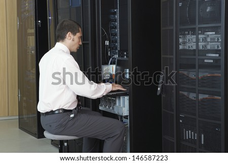 Young network engineer working in server room