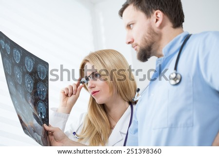 Young neurologists reading brain MRI at hospital - stock photo
