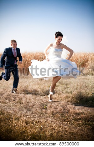 Young newly married couple chasing each other in field - stock photo