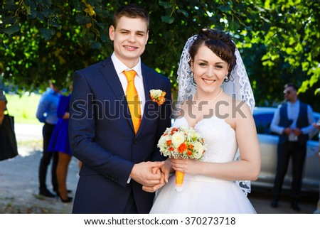 Young Newlywed Couple, holding wedding bouquet In hands. City park background