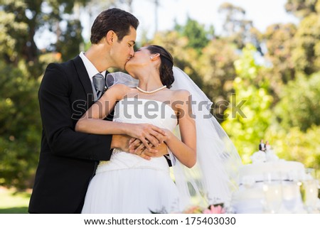 Young newlywed couple kissing besides wedding cake at the park - stock photo