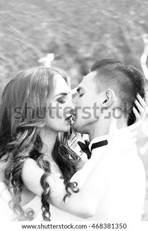 Young newlywed couple kissing in wedding cloth in forest decorated with ribbons outdoor, black and white