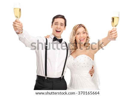 Young newlywed couple making a toast towards the camera with white wine isolated on white background - stock photo