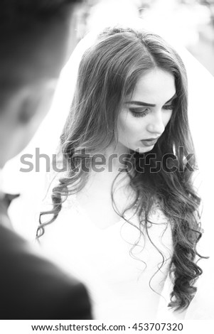 Young newlywed couple of woman in wedding dress and man embracing outdoor, black and white