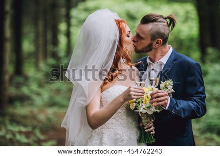 Young newlyweds clinking glasses and enjoying romantic moment together at forest park. Bride with red hair.