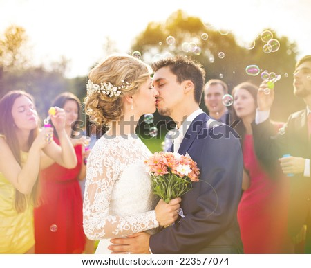 Young newlyweds kissing and enjoying romantic moment together at wedding reception outside, wedding guests in background blowing bubbles - stock photo