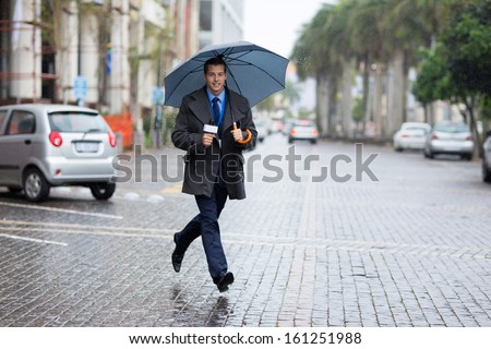 young news correspondent rushing for breaking news in raining day - stock photo