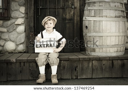 Young newsboy sitting down with a newspaper for sale; copy space for headline - stock photo