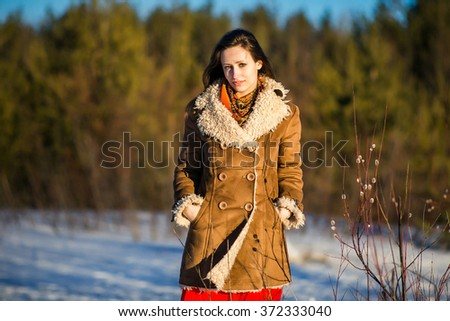 Young nice blond woman clothed sheepskin coat and scarf.  Spring time.