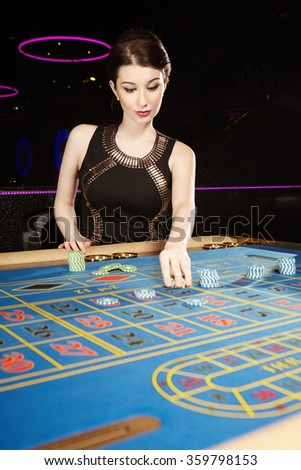 Young nice brunette gaming lady with roulette table