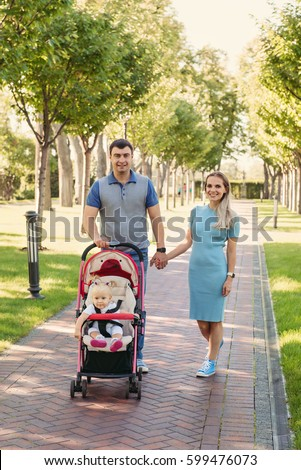 stock photo young nice couple walking with baby girl in a carriage on green park road 599476073