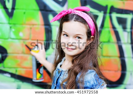 Young nice fashionable kid girl in near the graffiti wall - stock photo