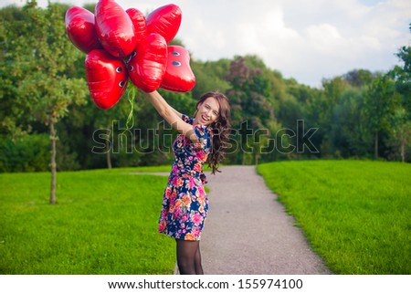 Young nice girl in beautiful dress with red balloons have fun outdoor