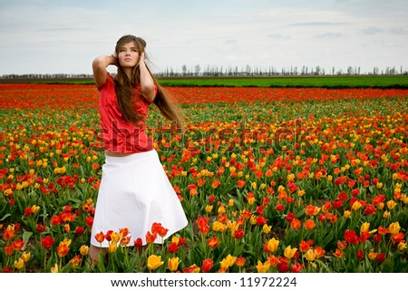 Young nice girl standing in red and orange tulips field - stock photo