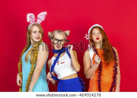 Young nice girls have fun on a christmas party. On red background.