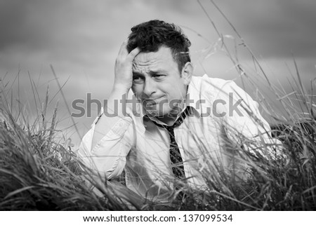Young, nice man sitting in the meadow, her head propped on her hand. He can not even believe what happened. He's in shock. - stock photo