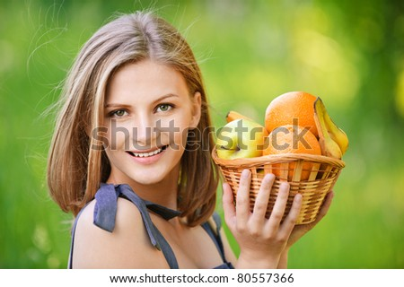 Young nice woman holds basket with fruit and pleasant smile, on green background of summer city park.