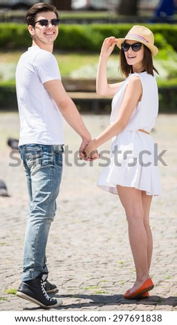 Young nifty couple walking along the street of european city. Full length. - stock photo