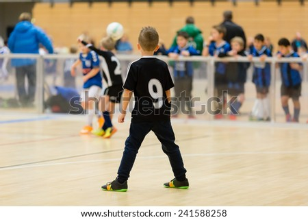 Young northern european boys playing a indoors soccer training match inside an indoor sports arena. - stock photo