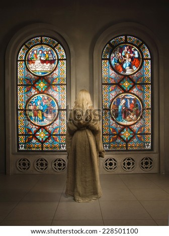 Young novice nun praying in a medieval church