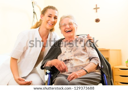 Young nurse and female senior in nursing home, the old lady sitting in a wheel chair - stock photo