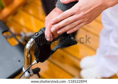 Young nurse and female senior with walking frame, cropped image - stock photo
