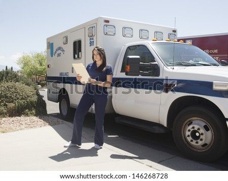 Young nurse assisting with paramedic ambulance and fire rescue services on scene in residential neighborhood for emergency medical call.  - stock photo