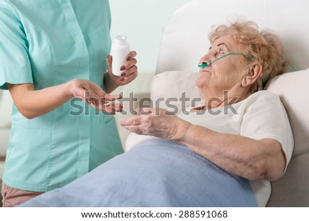 Young nurse giving the pills to her sick older patient - stock photo