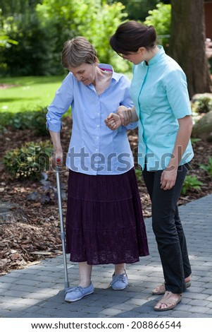 Young nurse goes for a walk with the old lady on crutches