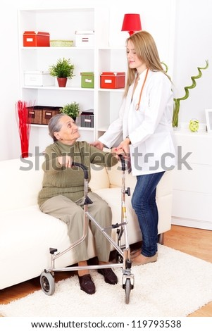 Young nurse helping elderly woman at home - stock photo