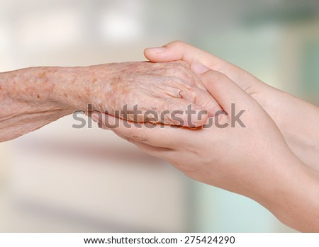 Young nurse holding old patient hand in hospital - stock photo