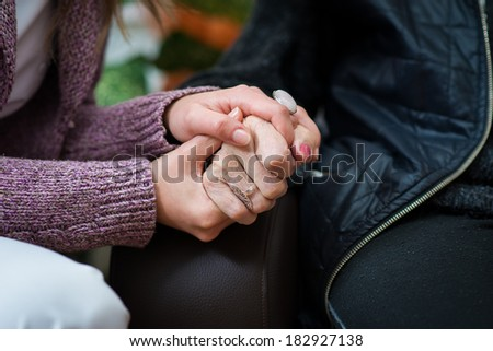 Young nurse holds the old woman hands