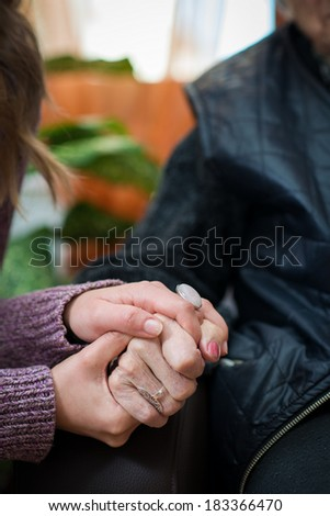Young nurse holds the old woman hands - stock photo