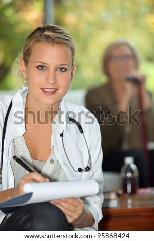 Young nurse in a care home - stock photo