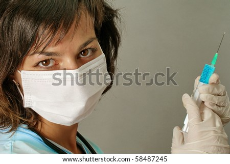 Young nurse in mask with syringe
