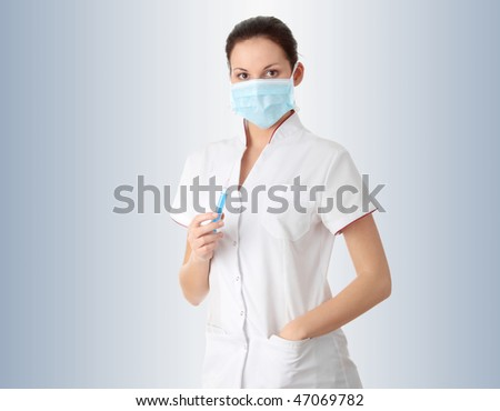 Young nurse in mask with syringe,  over gray background - stock photo