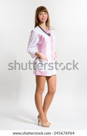 Young nurse in short medical gown with stethoscope - stock photo