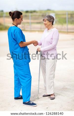 young nurse in uniform talking to senior woman outdoors - stock photo