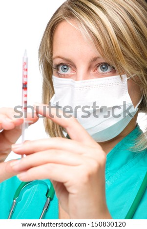 Young nurse is preparing syringe for injection while wearing surgical mask, isolated over white - stock photo