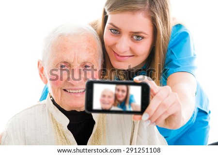Young nurse taking a selfie to ensure the family about the good condition of the grandmother. - stock photo