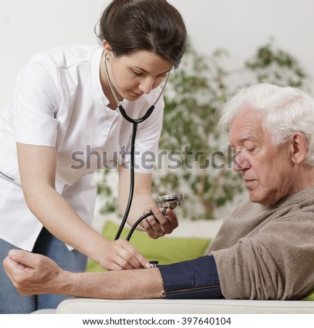 Young nurse taking blood pressure - stock photo