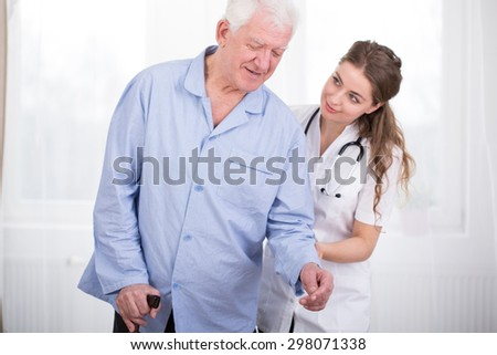 Young nurse taking care of an elder man