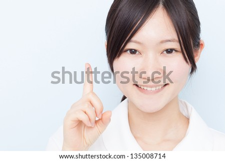 Young nurse woman pointing copy space, against pale blue background