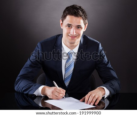 Young of businessman signing contract paper at desk against black background - stock photo