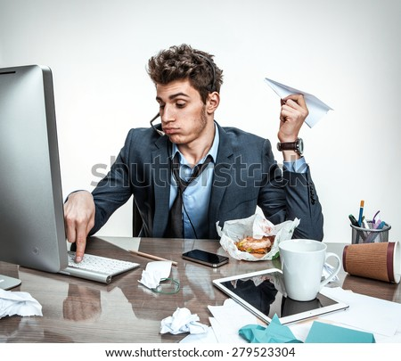 Young office man with paper plane in his hand typing on a computer keyboard / modern office man at working place, sloth and laziness concept - stock photo