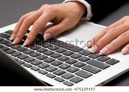 Young office woman in the black suite and with manicure is holding two hands on the laptop keyboard