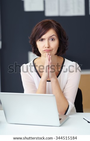Young Office Woman Sitting at her Desk with Laptop, Looking at the Camera with Confused Facial Expression. - stock photo